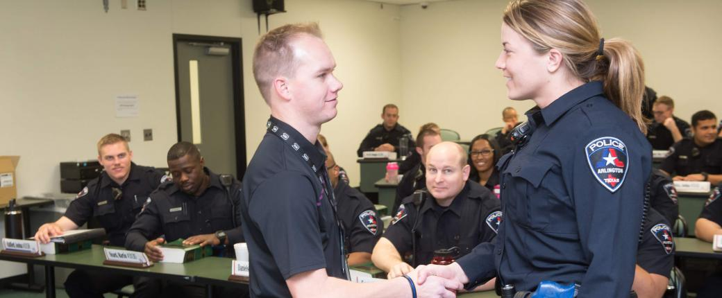 male officer shaking hands with female trainee