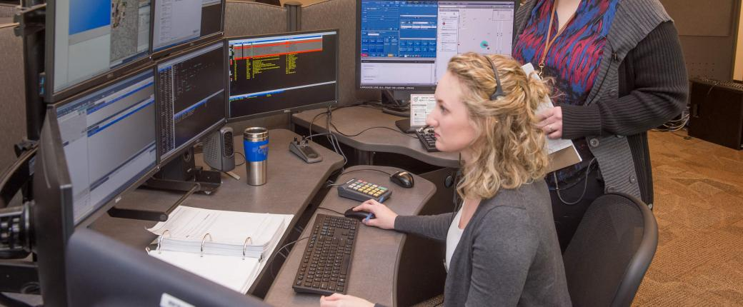 Two employees overlooking dispatch computers in station