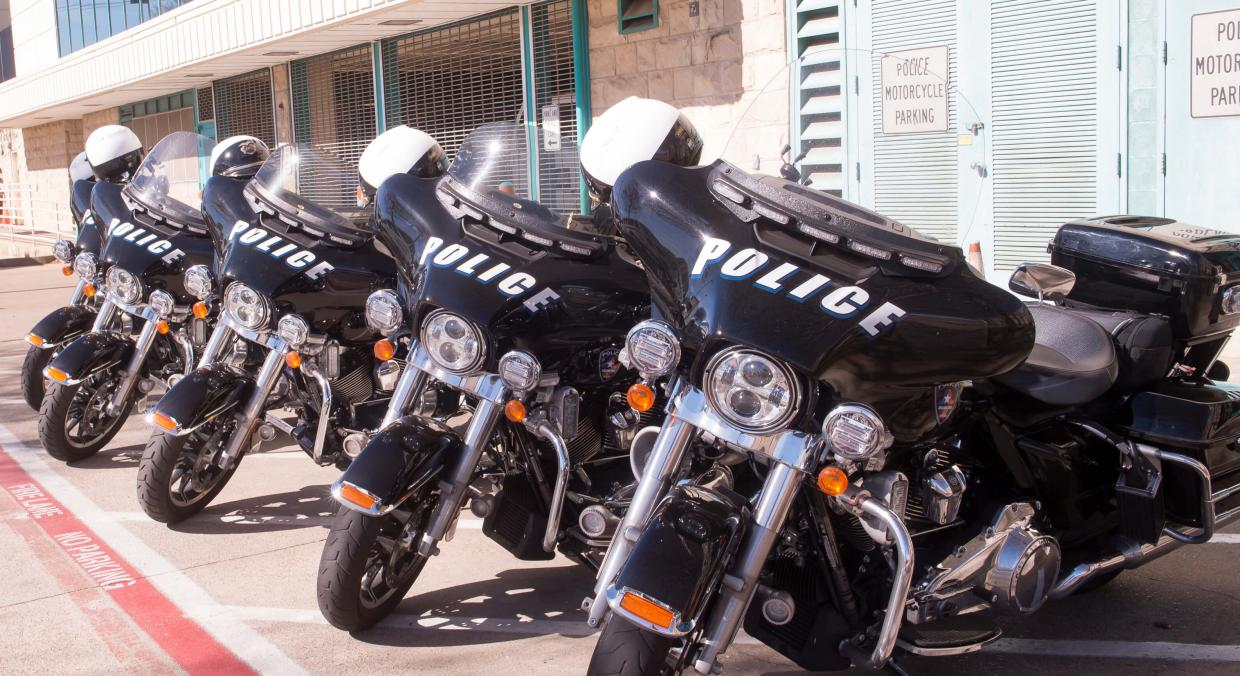 police motorcylces parked in a row out front of the station