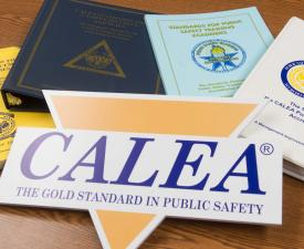 CALEA sign and CALEA documents and manuals resting on a table